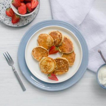 cottage cheese pancakes in a circle on white plate with strawberries