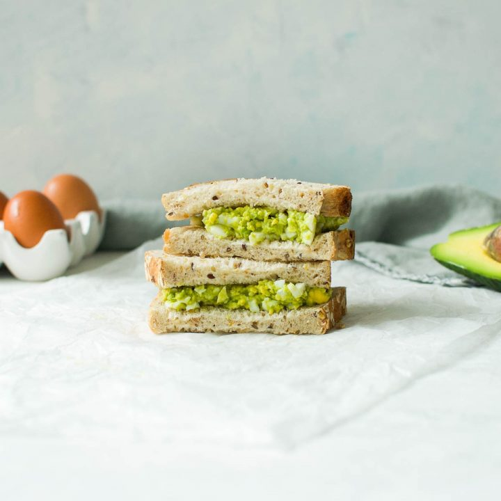 two egg and avocado sandwiches piled on top of each other with eggs and avocado in the background