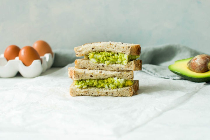 two avocado and egg sandwiches piled on each other