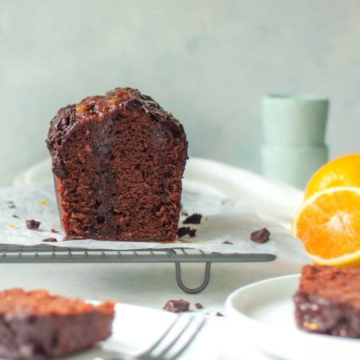 cut eggless chocolate cake on cooling rack with sliced oranges behind