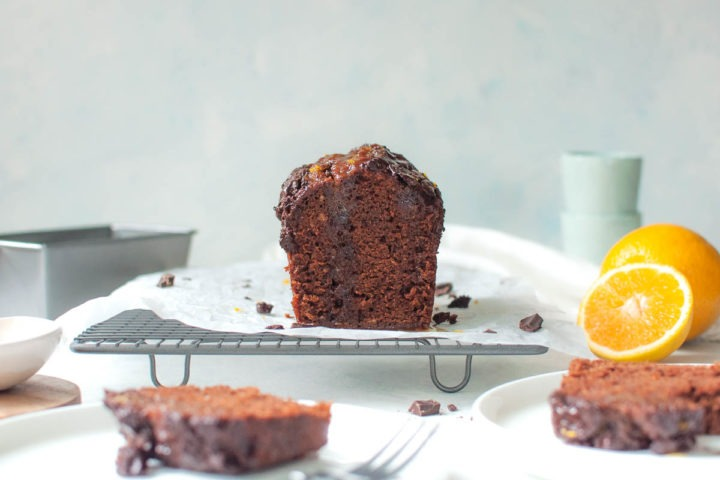 chocolate cake cut side facing with oranges and baking tin in background