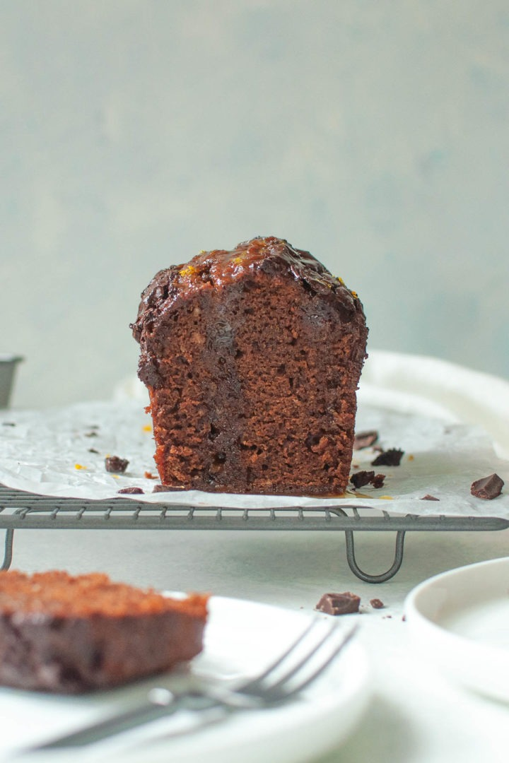 a slice of chocolate cake in the foreground and the cut cake in the background with visible orange drizzle