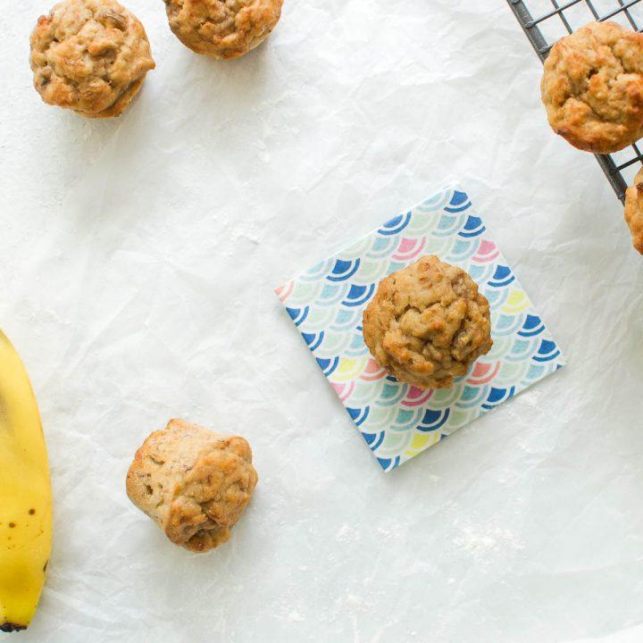 banana muffins on white background with banana in bottom left hand corner
