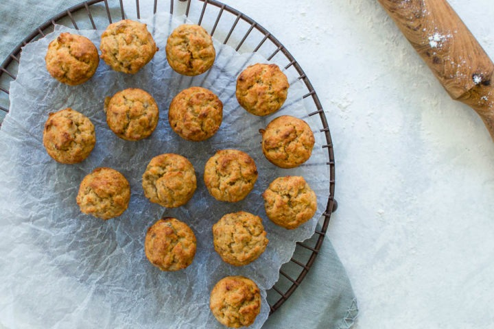 banana muffins on circular wire cooling rack with rolling pin in top right hand corner