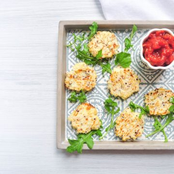 tray of cauliflower cheese bites sprinkled with rocket and served with tomato dip
