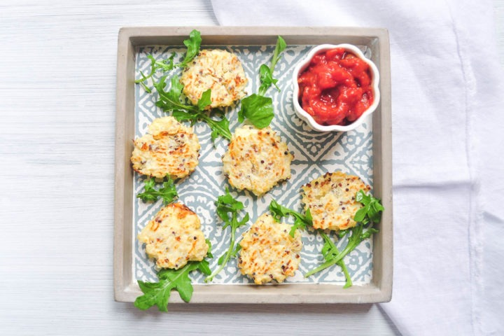 cauliflower cheese bites on tray in centre of picture with tomato dip in top right hand corner