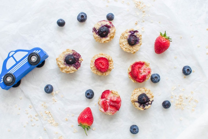 porridge bites topped with strawberries and blueberries on white background