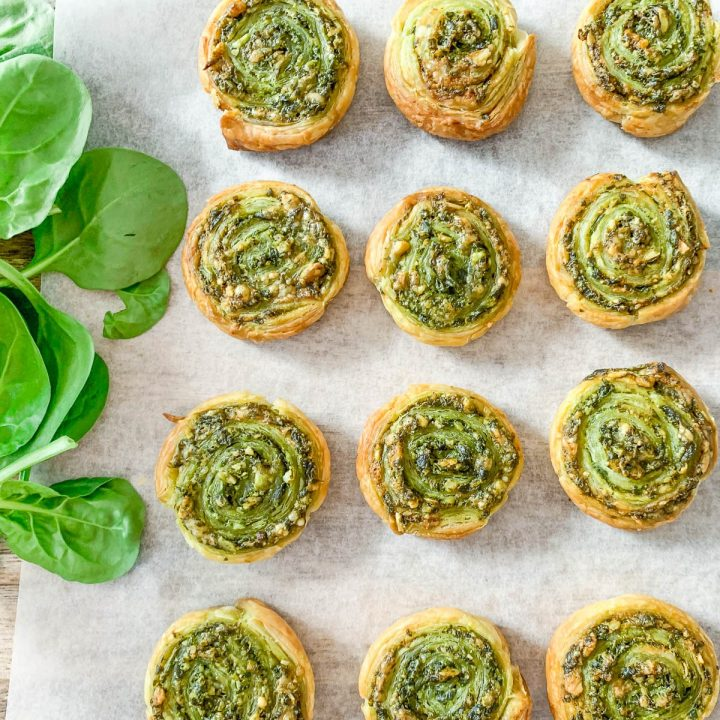 pinwheels in rows on white background with baby spinach on left side