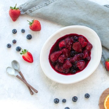 white bowl filled with berry compote with blueberries and strawberries scattered around