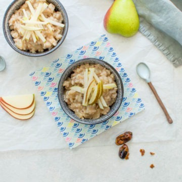 two blue bowls of rice pudding with sliced pear next to them