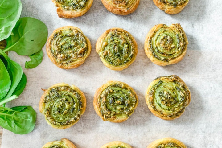 puff pastry pinwheels on tray with baby spinach on left side