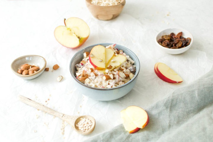 bircher muesli in a pale blue bowl decorated with cut apples