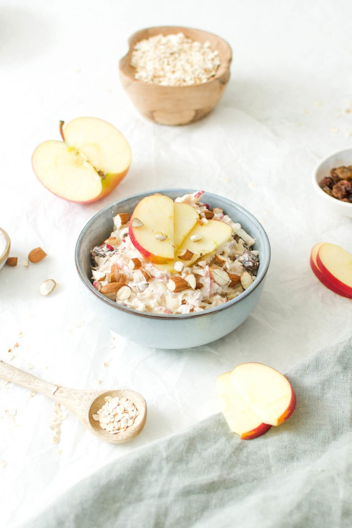 bircher muesli topped with apple slices with apple halves and oats dotted around in the background
