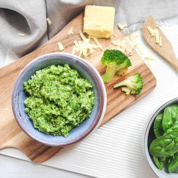 blue bowl filled with broccoli spinach pesto on wooden board with spinach, cheese, and broccoli florets to the right of the bowl