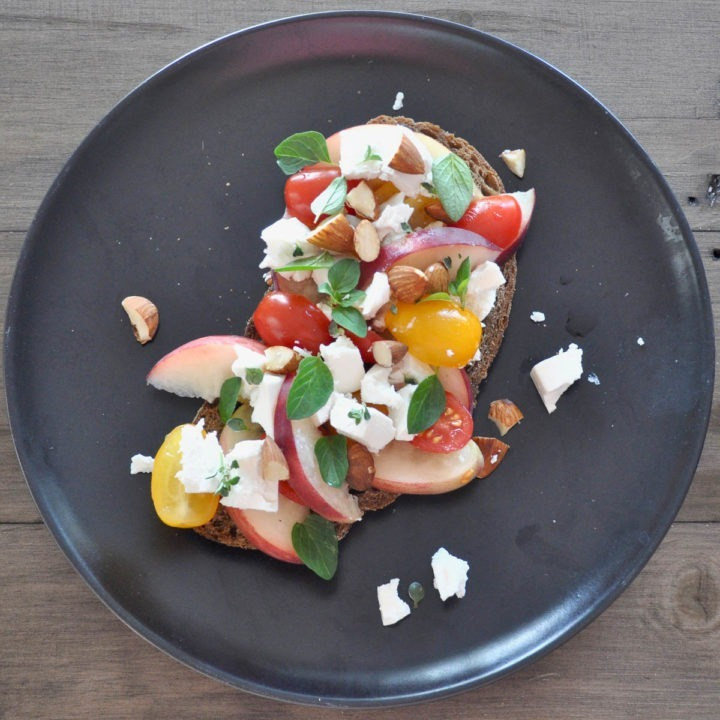 toast topped with feta, peaches, red and yellow tomatoes and herbs on a black plate