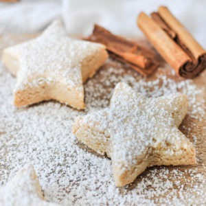 close up of two German cinnamon stars dusted with icing sugar with cinnamon sticks in the background
