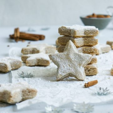 a stack of five zimtsterne cinnamon stars with one placed on its edges to show the icing