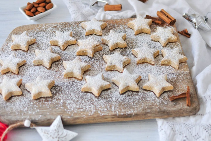 zimtsterne cinnamon stars on a wooden board dusted with icing sugar with cinnamon sticks and almonds scattered around the edges