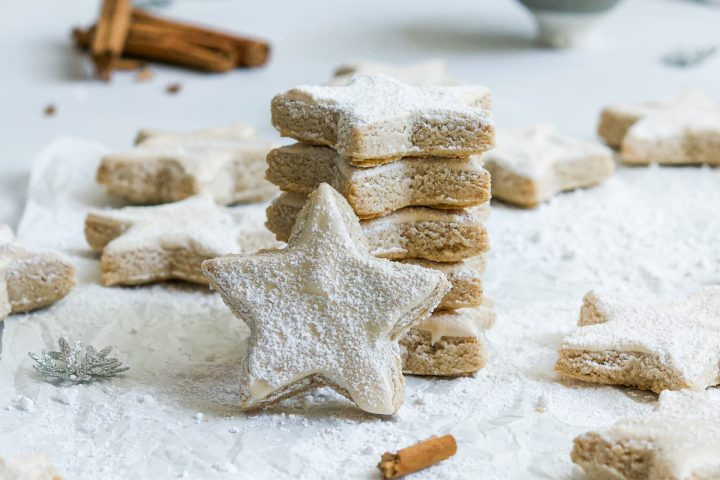 stack of cinnamon stars zimsterne with one in front to show the icing. Cinnamon sticks in the background