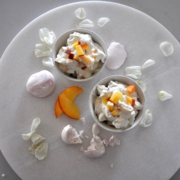 two bowls of peach eton mess with pink meringues and white rose petals