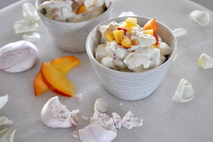 side shot of white bowl of peach eton mess surrounded by pink meringues and white rose petals