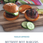 two mini beetroot beef burgers in buns on a wooden board