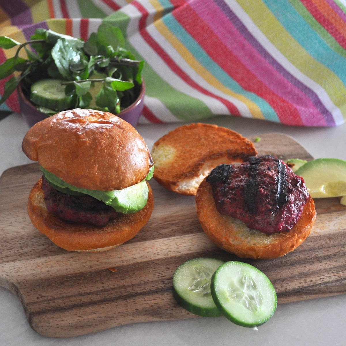two mini beetroot beef burgers in buns with cucumber and avocado
