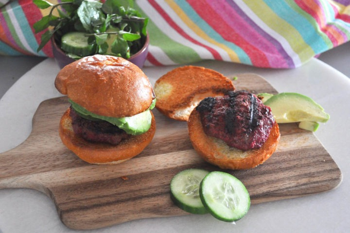 mini beef burgers in buns with cucumber on a wooden board