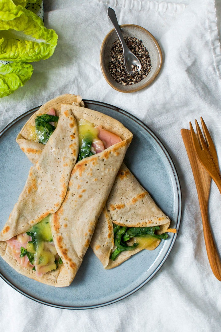 long image of ham and cheese galettes on a pale blue plate with lettuce in the top left corner