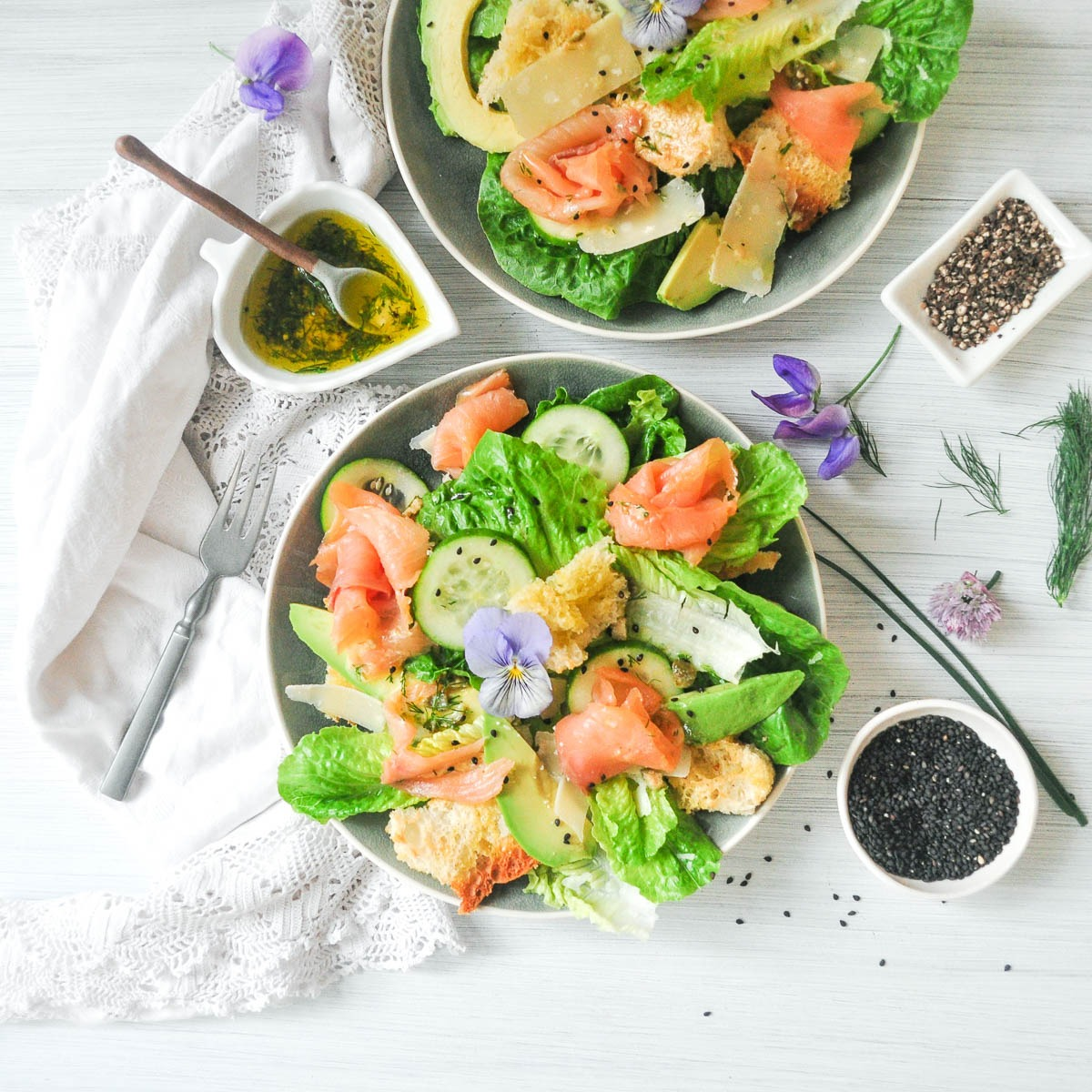 smoked salmon caesar salad on blue plate decorated with purple edible flowers on and around the salad
