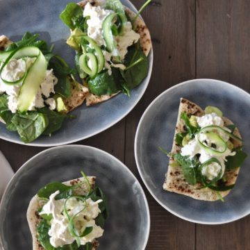 naan bread on blue plates topped with spinach, chicken salad and finished with cucumber ribbons