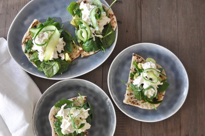 curried chicken salad on naan with spinach and cucumber ribbons on three plates