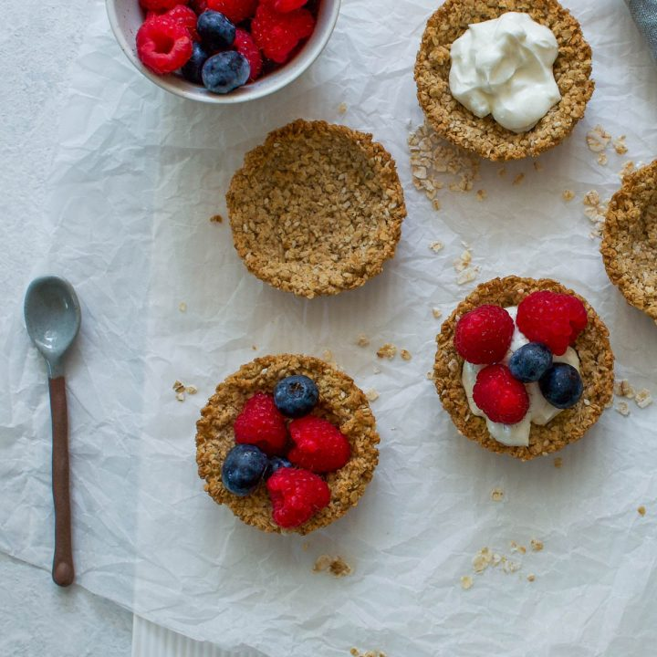 five granola cups, on partly hidden, three filled with yogurt and two with raspberries and blueberries