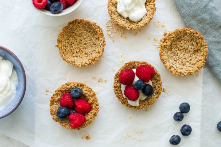 granola cups on white background scattered with oats, some with yogurt and berries, others left plain