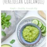 easy avocado dip Guasacaca in blue bowl with slices of cucumber next to it and coriander and avocado in the image