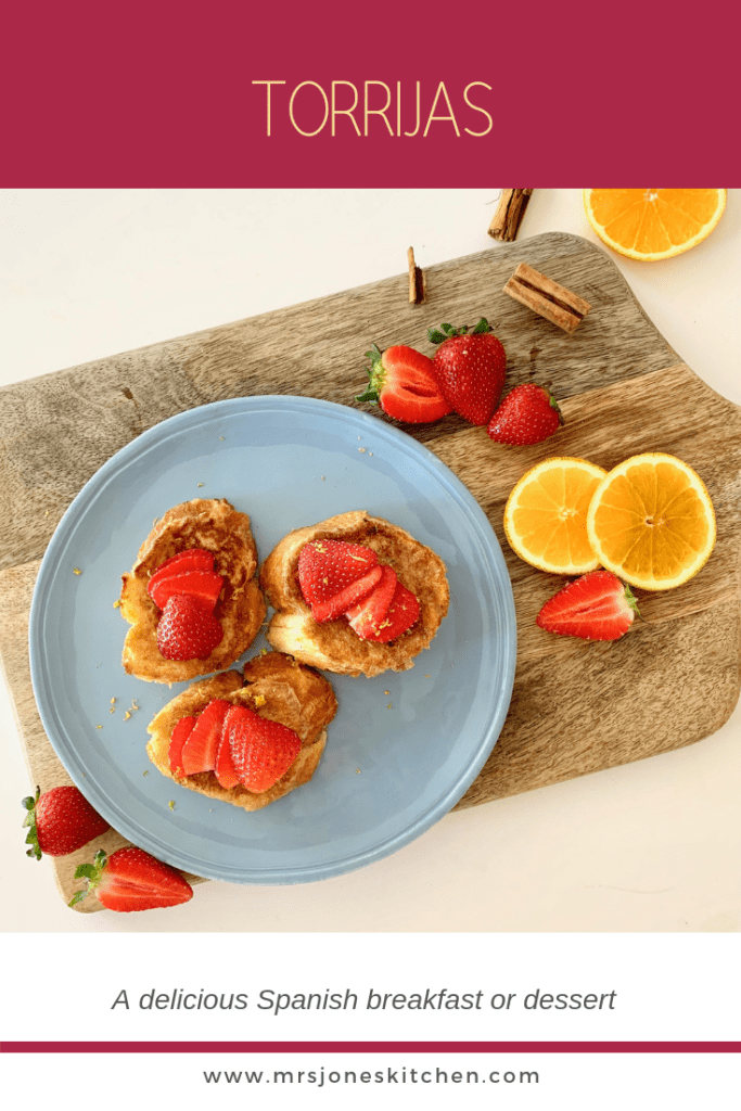 blue plate on wooden board with three slices or torrijas topped with strawberries