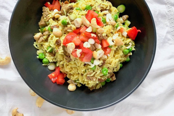 black bowl in middle of image filled with pilaf and topped with fresh tomatoes and cashews