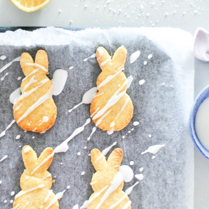 lemon shortbread biscuits in the shape of rabbits with white icing drizzled over them