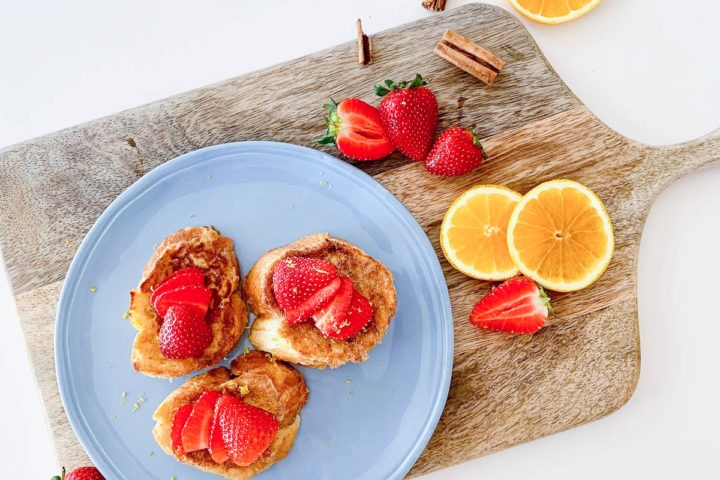 torrijas on light blue plate on wooden board with strawberries, cinnamon sticks and orang slices