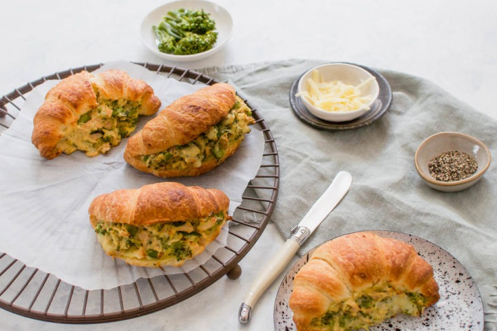 four tuna melt croissants, one on a plate and the other three on round cooling rack, with broccoli and grated cheese in the background