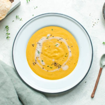 a white bowl of vegan creamy carrot soup sprinkled with thyme