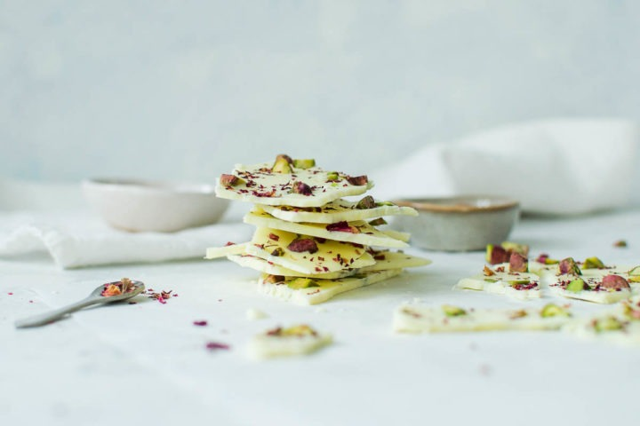 pile of white chocolate bark with bark to the right and small spoon of rose petals to the left