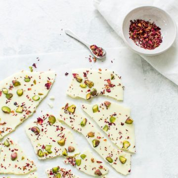 white chocolate bark broken into pieces sprinkled with rose petals and pistachios with bowl of pink rose petals top right hand corner