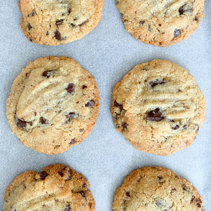 overhead shot of six chocolate chip cookies in two vertical rows on white background