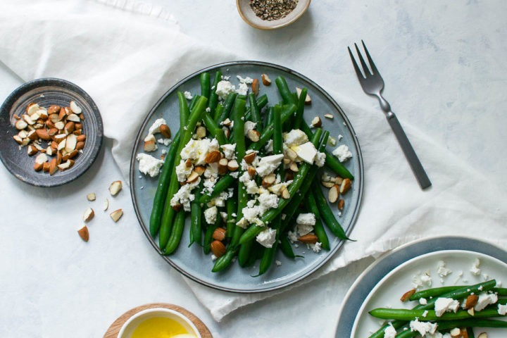 green bean salad with feta and almonds in middle of picture on blue plate with grey bowl of chopped almonds to the left and for to the right