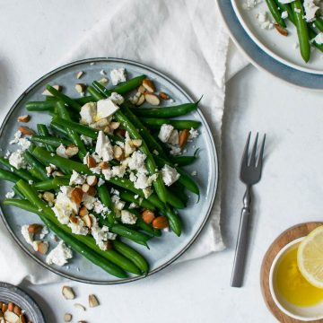 green beans topped with feta and almonds on blue plate with lemon vinaigrette in white bowl bottom right corner