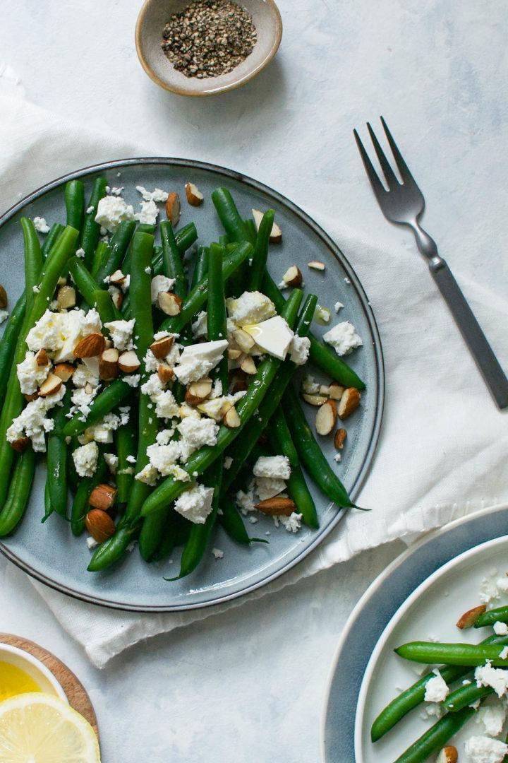 vertical image of green bean salad on white background with lemon dressing bottom left corner