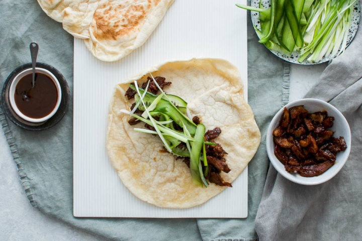 crispy leftover roast lamb is mixed with hoisin sauce and place in centre of bread wrap with cucumber and spring onion. More hoisin lamb is to the right of the wrap