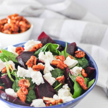 beet and feta salad with sweet spicy walnuts in blue bowl