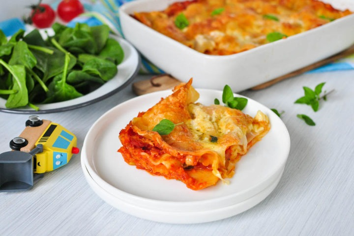 side view of portion of lasagne showing the layers of red lentil sauce and pasta